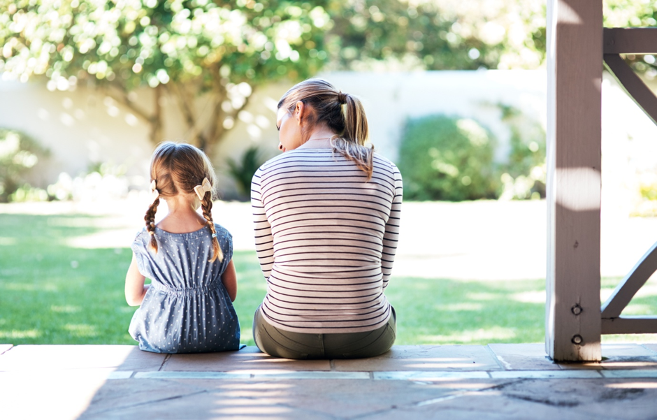 A mother and daughter sitting together on a house porch as they talk to each other about their feelings
